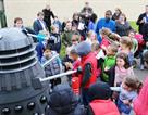 A picture of children surrounding the Dalek